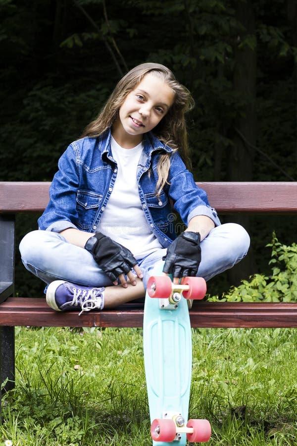 牛仔裤衬衣的美丽的白肤金发的青少年的女孩,坐与背包和滑板的长凳在公园 库存图片