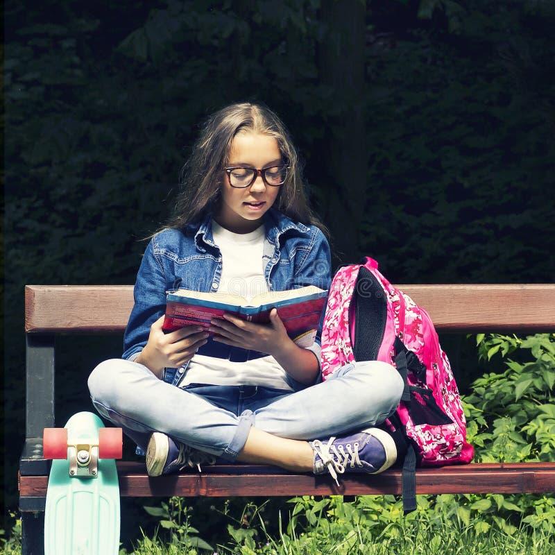 牛仔裤衬衣的美丽的白肤金发的青少年的女孩读书的在与一个背包和滑板的长凳在公园 库存图片