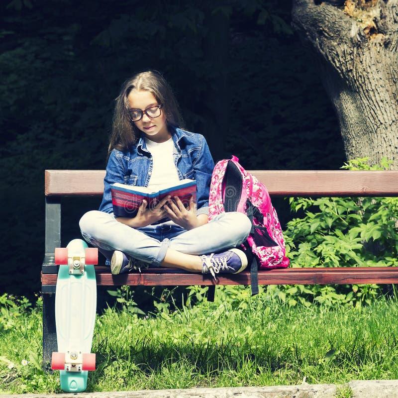 牛仔裤衬衣的美丽的白肤金发的青少年的女孩读书的在与一个背包和滑板的长凳在公园 免版税图库摄影