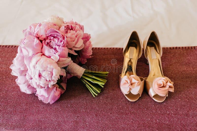 牡丹和美丽的鞋子Bouquete在桃红色背景 婚礼bouquete和鞋子有高跟鞋的 新娘` s辅助部件 Weddi 免版税图库摄影