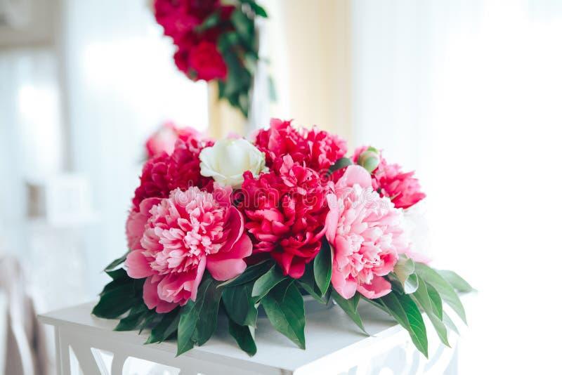 牡丹在餐馆,桌设置放逐 背景钮扣眼上插的花看板卡装饰装饰邀请婚姻白色的珍珠玫瑰 红色花在餐馆 库存照片