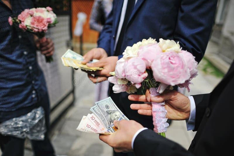 牡丹婚礼花束在新郎的手的有金钱的 Redempti 免版税库存照片
