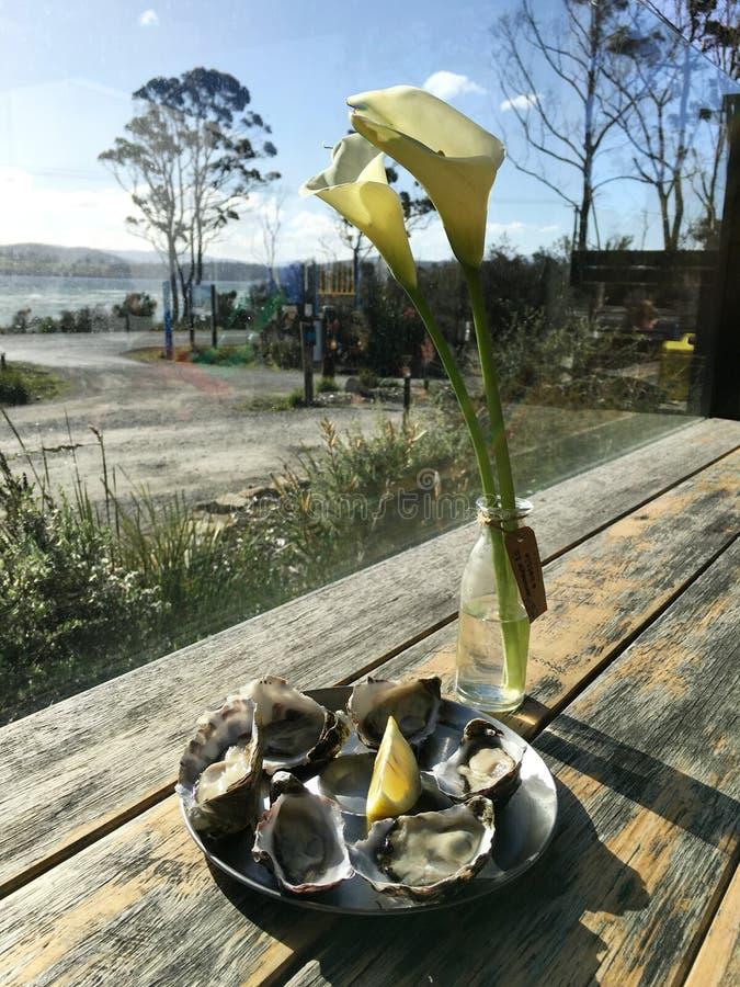 牡蛎板材与白色水芋百合的在后面 免版税库存图片