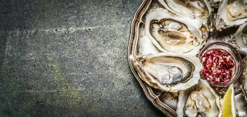 牡蛎用柠檬和青葱在土气背景,顶视图,文本的地方调味 免版税图库摄影