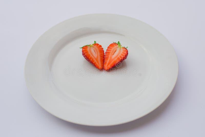 牡鹿在一块白色板材对分和装饰的塑造了,新鲜,有机草莓 免版税库存照片