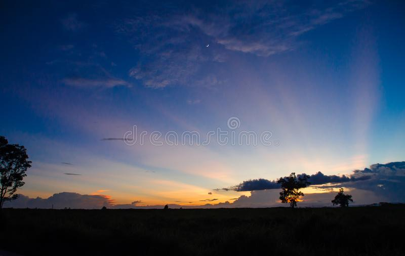 牧场地剪影有五颜六色的日落背景 库存图片