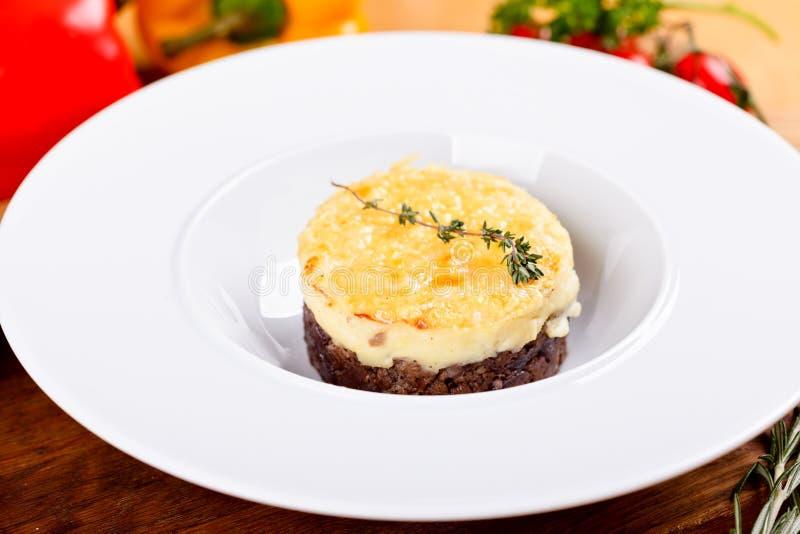 牧羊人` s饼 传统英国盘用肉末、土豆泥和乳酪在白色板材 免版税库存图片