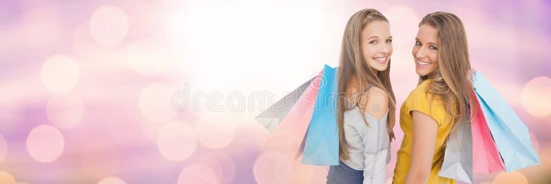 购物与袋子和闪耀的光bokeh转折的妇女朋友 免版税库存图片