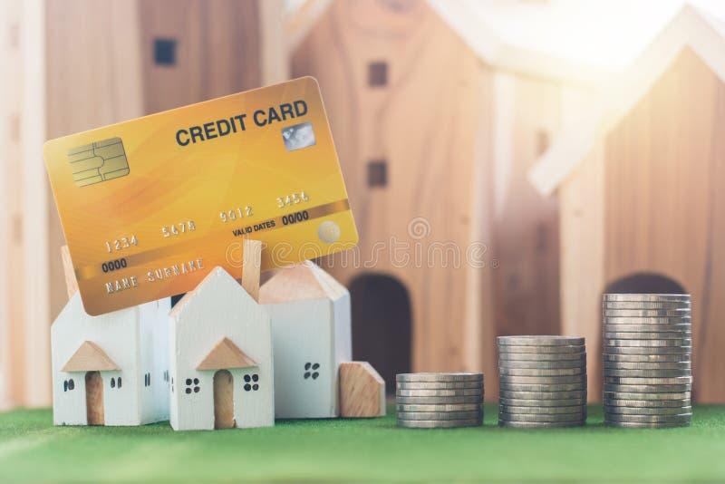 物产投资、微型房子模型与信用卡和金钱硬币堆在模仿草 库存图片
