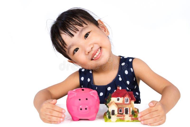 物产概念的亚洲矮小的中国女孩挽救金钱 库存图片