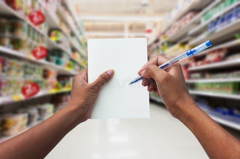 购物和拿着空的笔记本的手妇女 库存照片