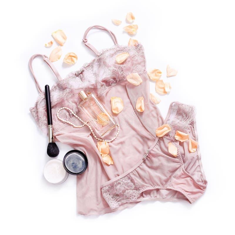 购物和时尚概念 套有化妆产品的迷人的时髦的性感的鞋带女用贴身内衣裤,香水,花瓣 免版税库存照片