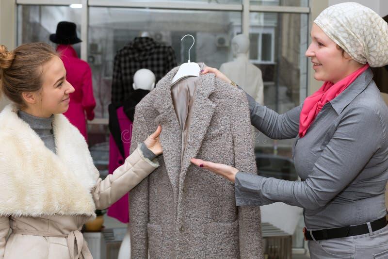 购物在百货大楼顾客和女售货员互动 免版税库存照片