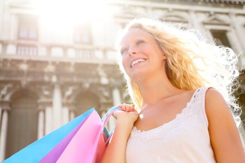 购物妇女愉快的举行的购物袋,威尼斯 免版税库存照片