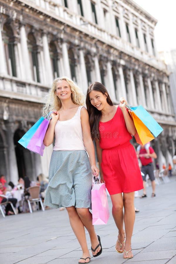 购物妇女走满意对袋子,威尼斯 免版税库存照片