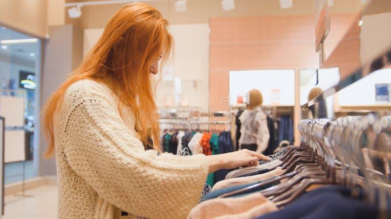 购物妇女-妇女选择外套 免版税图库摄影