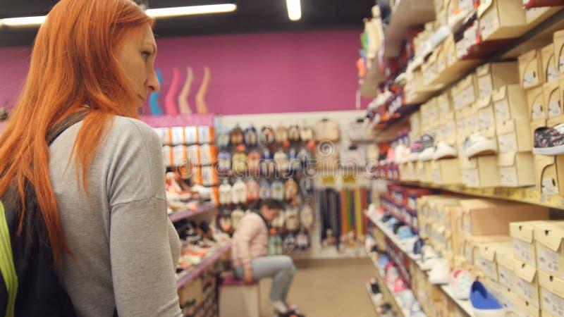 购物妇女-少妇选择在购物中心的鞋子 免版税库存照片