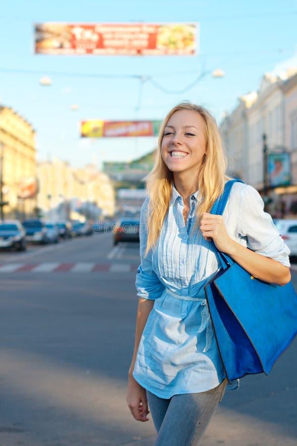 购物微笑的女孩户外 免版税图库摄影