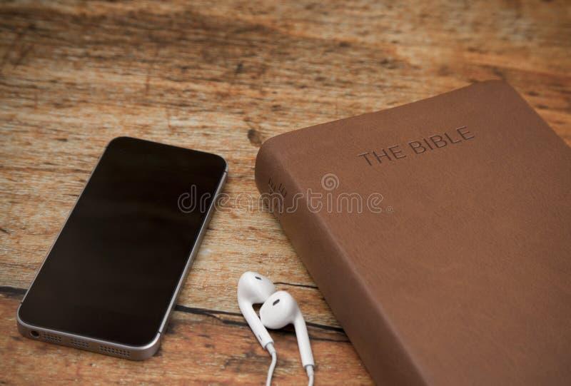 物理圣经和一个巧妙的电话有耳机的 免版税库存图片