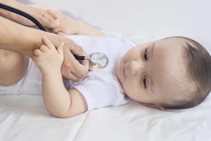 物理核对 婴孩的核对 审查有听诊器的儿科医生小男孩 审查六个月老的医生 库存照片