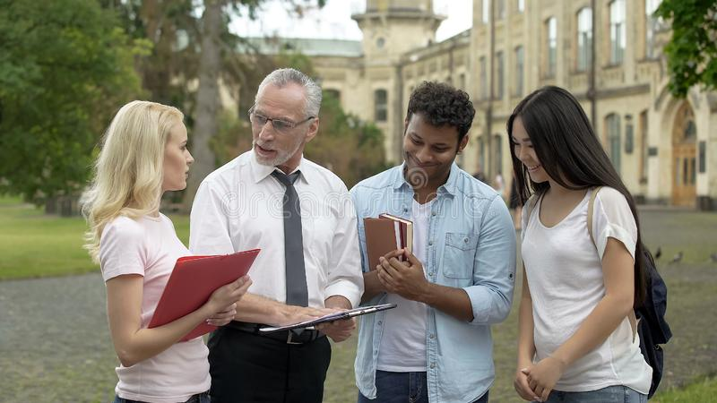 物理老师谈论科学研究与小组学生,配合 库存照片