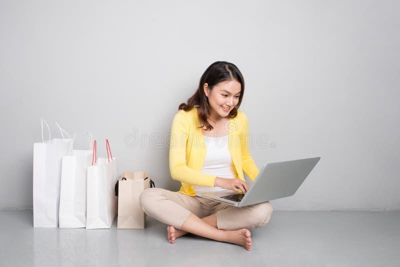 购物年轻亚裔的妇女在家在网上坐除行以外  免版税图库摄影