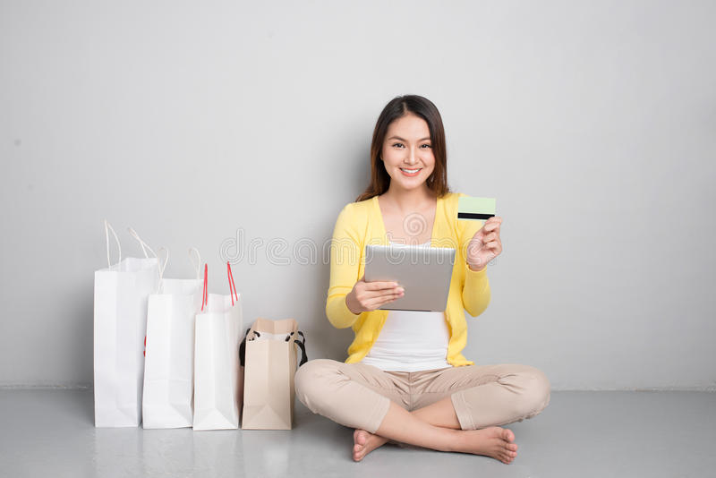 购物年轻亚裔的妇女在家在网上坐除行以外  库存图片