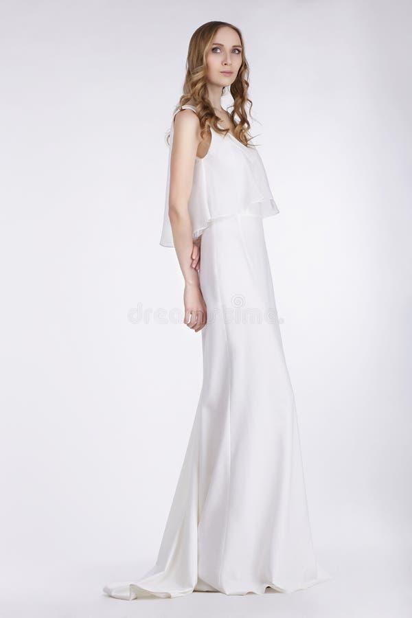 阴物 站立在白色礼服的逗人喜爱的少妇 免版税图库摄影