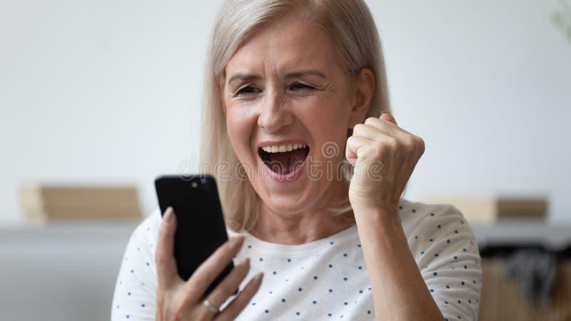 特写兴奋的老妇人大喊大叫,用电话庆祝成功 免版税库存图片