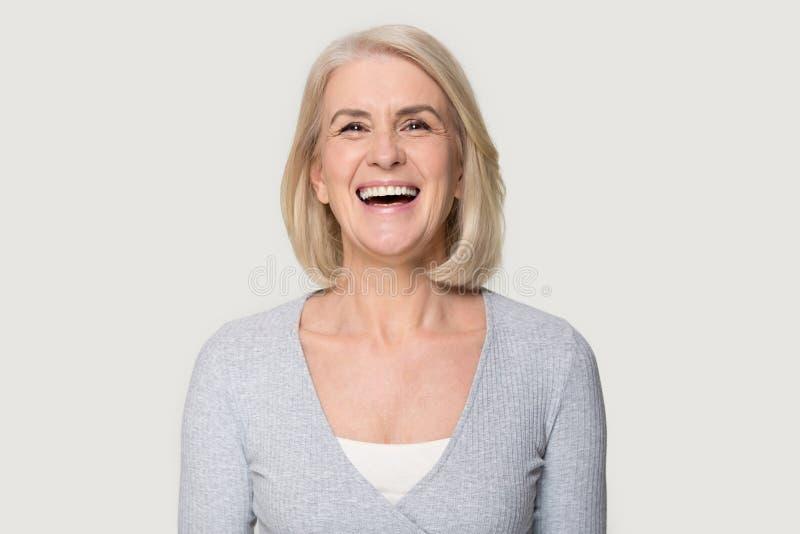 特写愉快年迈的女性笑的摆在灰色演播室背景 免版税库存图片
