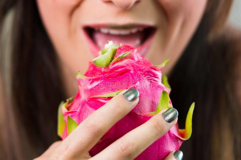 特写浅黑肤色的男人、黑暗的奥妙神色和绿色唇膏,阻止桃红色pitaya果子用面对照相机的两只手 库存图片