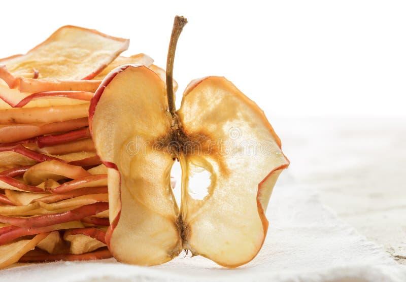 特写镜头一干苹果切片在垂直的堆在白色背景的苹果芯片附近站立 库存图片
