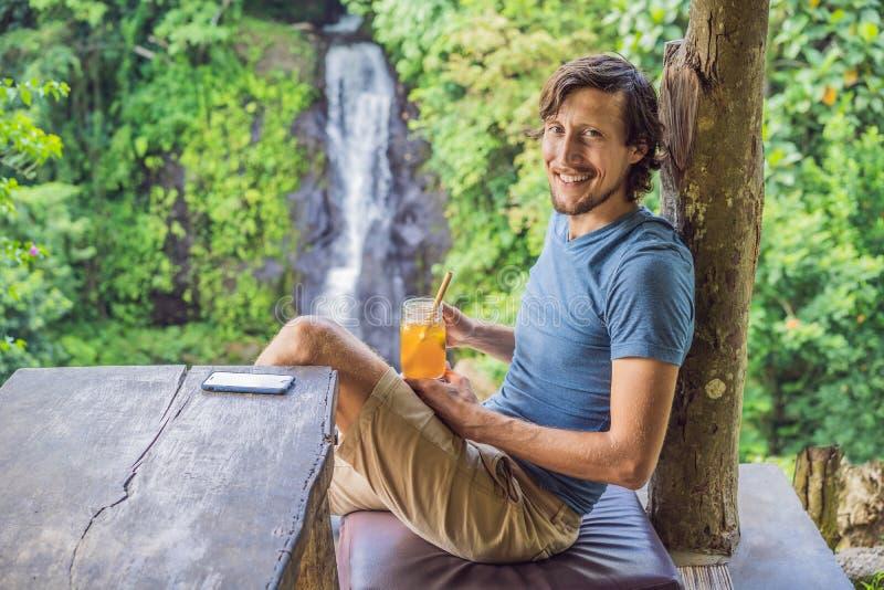 特写镜头一杯美丽的人饮用的冰茶的画象图象充满感觉的愉快在绿色自然和瀑布庭院里 免版税图库摄影