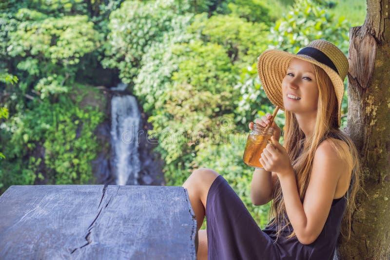 特写镜头一杯美女饮用的冰茶的画象图象充满感觉的愉快在绿色自然和瀑布庭院里 图库摄影