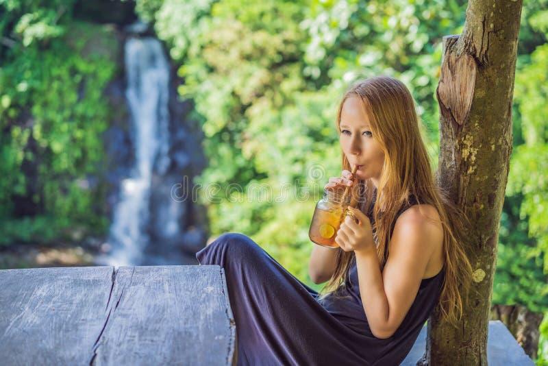 特写镜头一杯美女饮用的冰茶的画象图象充满感觉的愉快在绿色自然和瀑布庭院里 库存照片