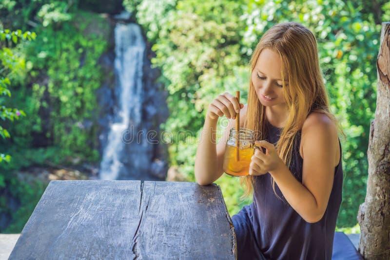 特写镜头一杯美女饮用的冰茶的画象图象充满感觉的愉快在绿色自然和瀑布庭院里 免版税库存照片