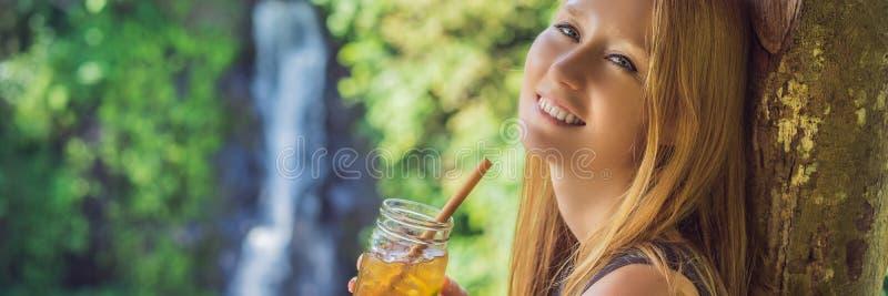 特写镜头一杯美女饮用的冰茶的画象图象充满感觉的愉快在绿色自然和瀑布庭院里 免版税库存图片