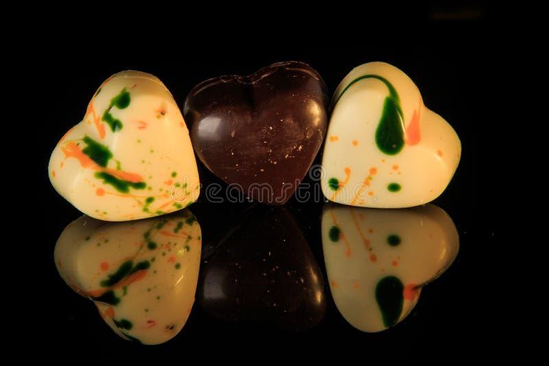 特写镜头三心形的糖果形成白色和黑巧克力 图库摄影