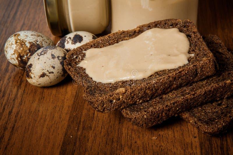 特写镜头三黑麦面包切片用在鹌鹑蛋旁边的tahini黄油 免版税库存图片