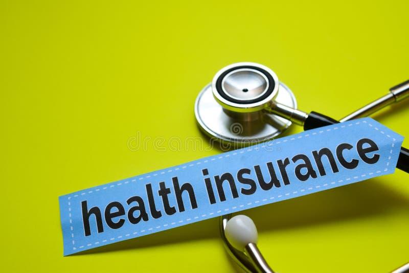 特写镜头与听诊器概念启发的健康保险在黄色背景 免版税库存照片