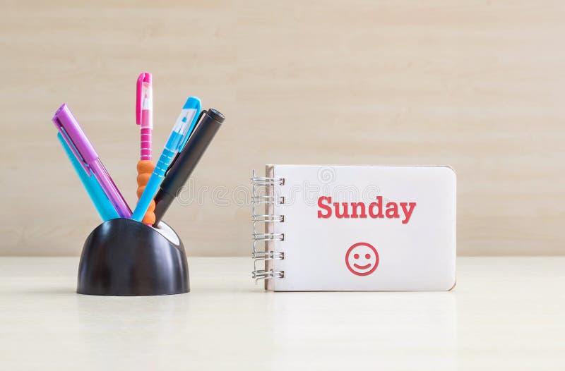 特写镜头与黑陶瓷书桌的颜色笔整洁为笔和红色星期天词在白页和愉快的面孔情感在笔记本o 库存照片