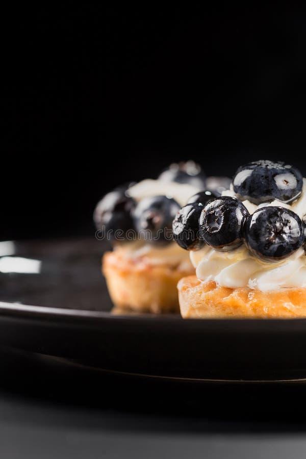 特写镜头两小蛋糕用蓝莓和乳脂状的奶油在一个黑色的盘子 免版税库存图片