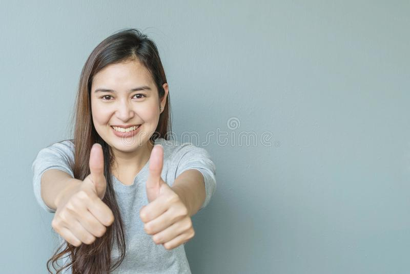特写镜头亚裔妇女与敬佩与微笑面孔的行动在与拷贝空间的被弄脏的水泥墙壁被构造的背景 库存图片