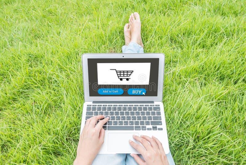 特写镜头亚裔妇女坐草地板在庭院构造了购物的背景在网上在妇女概念生活方式  免版税图库摄影