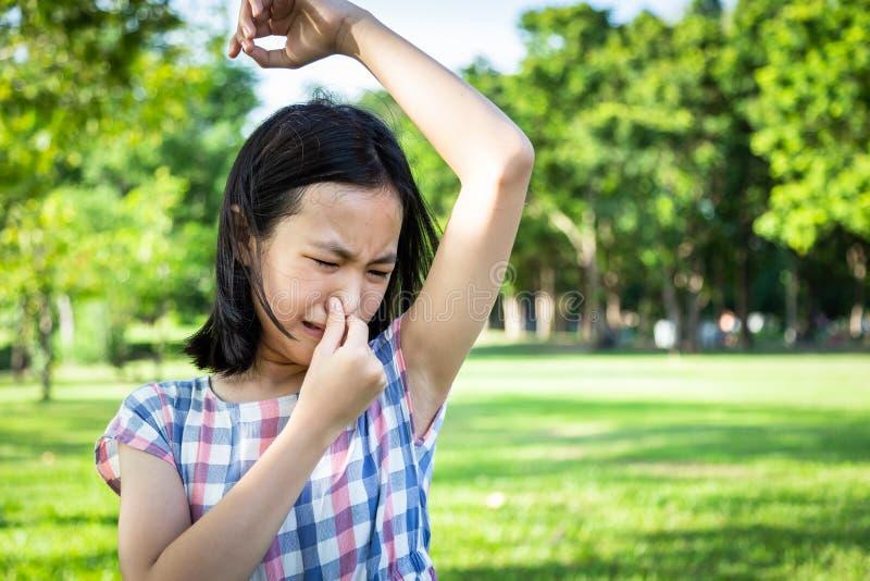 特写镜头亚裔逗人喜爱的女孩在室外公园感觉坏肮脏的气味情况,嗅到,嗅她的湿腋窝,漂亮的孩子 库存图片