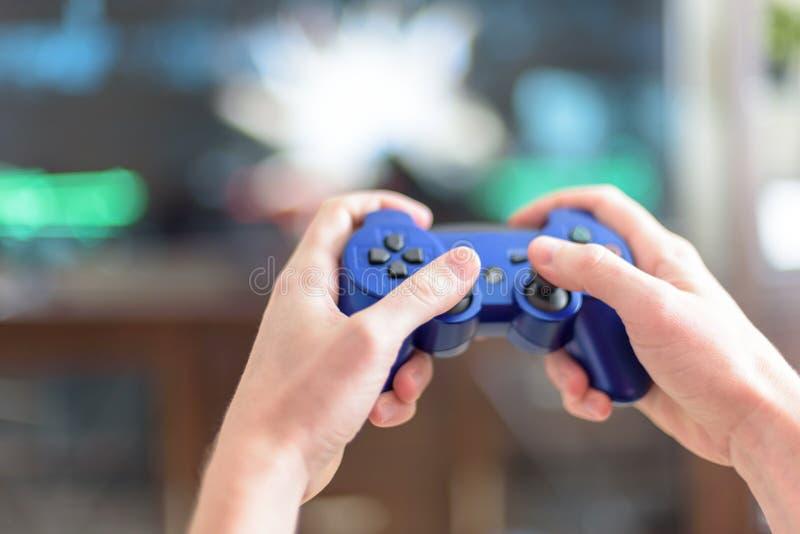 特写镜头人在电子游戏控制器的手 库存图片