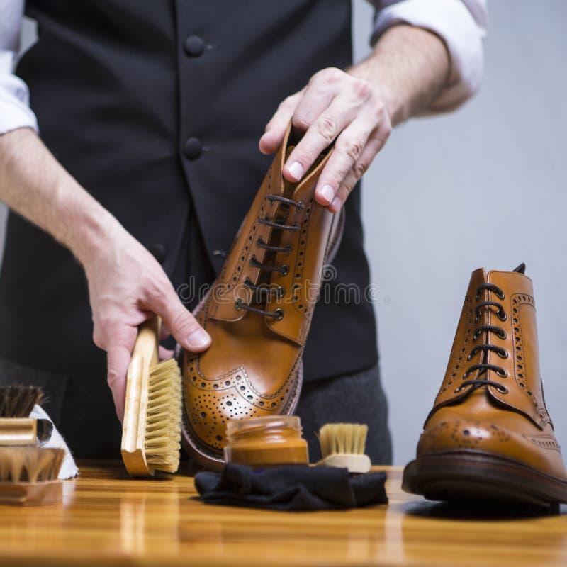 特写镜头人清洗豪华小牛皮革方的手与特别辅助部件和工具 图库摄影