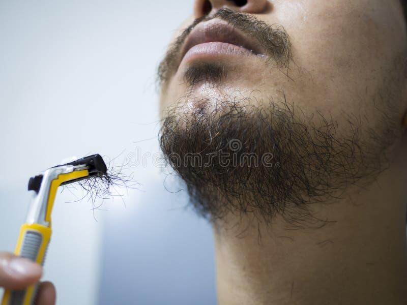 特写镜头人用途刮杂乱胡子和髭在他的面孔的黄色剃具在卫生间里 免版税库存照片