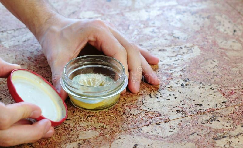 特写镜头人` s手打开瓶子用在厨房用桌上的霉隐蔽的切的柠檬 特写镜头顶视图 免版税图库摄影