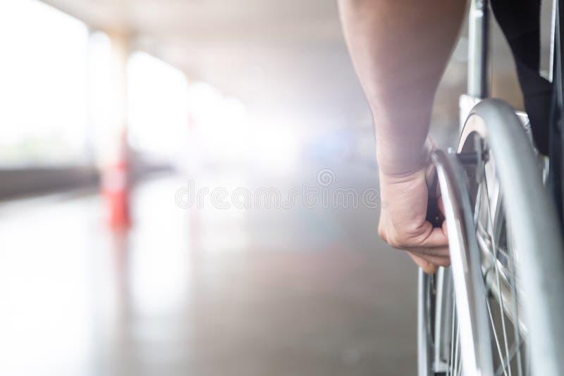 特写镜头使在轮椅轮子的人手失去能力  库存照片